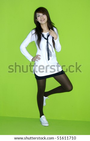 casual girl standing up over a  green - stock photo