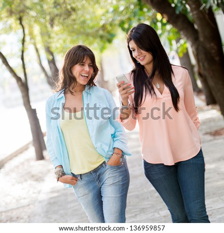 Casual girls walking outdoors using a mobile phone - stock photo