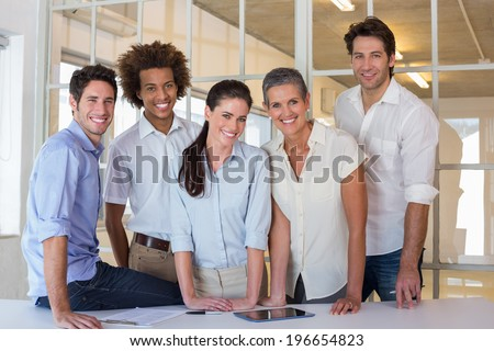 Casual group of coworker friends smiling at camera during business meeting - stock photo