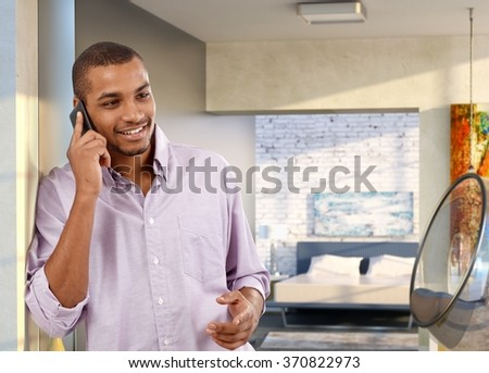 Casual handsome afro american man with mobile phone at trendy home. Standing against wall, smiling, happy, talking. - stock photo