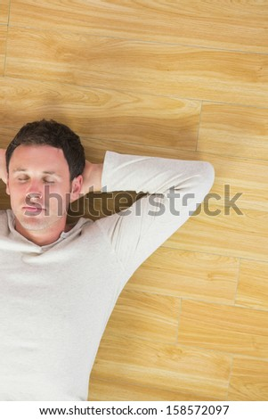 Casual handsome man lying on floor with closed eyes in bright room - stock photo