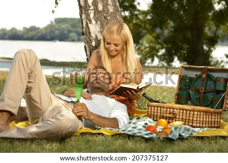 Casual handsome man sleeping at picnic in lap of attractive blonde girlfriend reading a book. Smiling, outdoor, basket. - stock photo