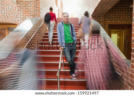 Casual handsome student standing on stairs in college - stock photo