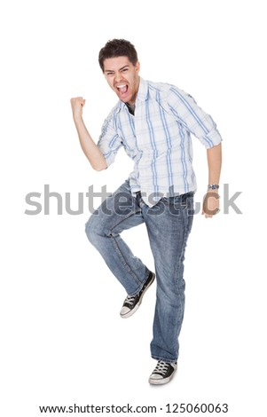 Casual handsome young man in jeans shouting for joy raising his hands above his head - stock photo