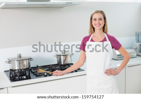 Casual happy blonde standing next to stove top  in bright kitchen - stock photo