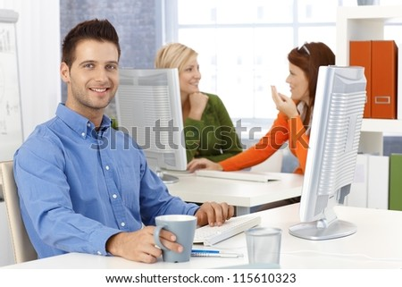 Casual happy businessman with sitting at desk in office, smiling at camera, with colleagues in background. - stock photo
