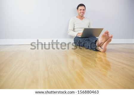 Casual happy man leaning against wall using laptop in bright room - stock photo
