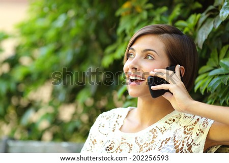 Casual happy woman on the phone in a park sitting on a bench with a green blurred background             - stock photo