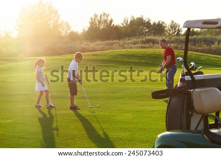 Casual kids at a golf field holding golf clubs studing with trainer. Sunset - stock photo