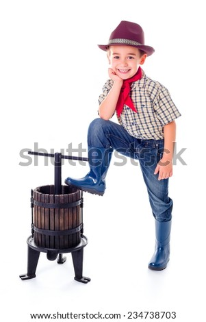 Casual little farmer boy posing with manual grape pressing tool - stock photo