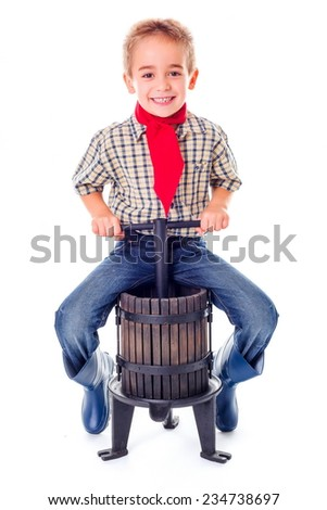 Casual little farmer boy sitting on manual grape pressing tool - stock photo