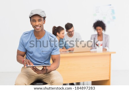 Casual male artist using digital tablet with colleagues in the background at a bright office - stock photo