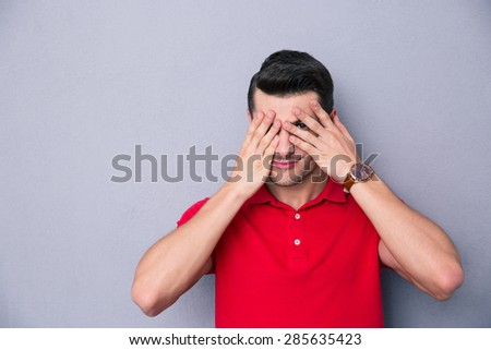 Casual man covering his eyes with fingers over gray background - stock photo