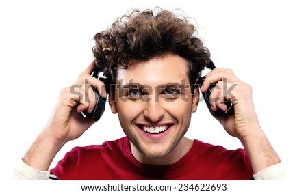 Casual man holding headphones over gray background - stock photo