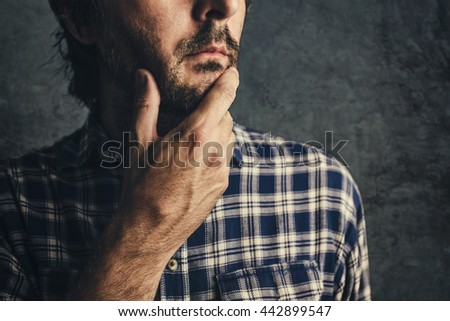 Casual man in plaid shirt thinking and contemplating, low key, selective focus portrait - stock photo