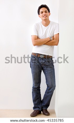 Casual man leaning on the wall and smiling - stock photo