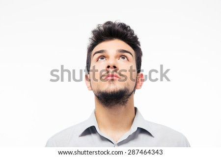 Casual man looking up at copyspace isolated on a white background - stock photo
