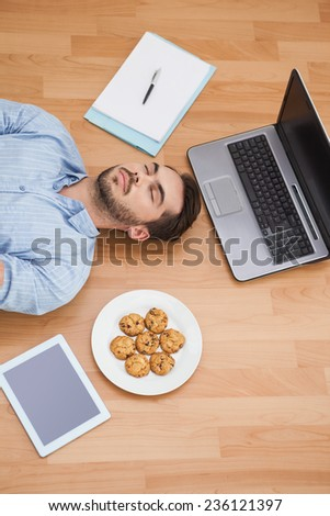 Casual man lying on floor surrounded by his possesions at home in the living room - stock photo