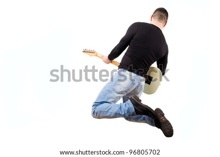 casual man playing an electric guitar and jumping - stock photo