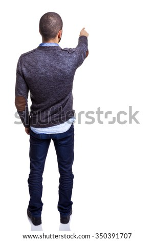 Casual man pointing to copyspace, isolated over a white background - stock photo