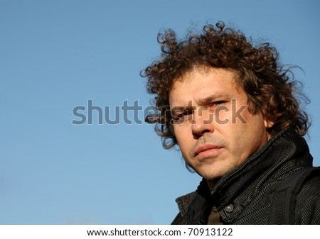 Casual man portrait with curly hair, sky background - stock photo