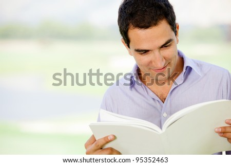 Casual man reading a book outdoors and smiling - stock photo