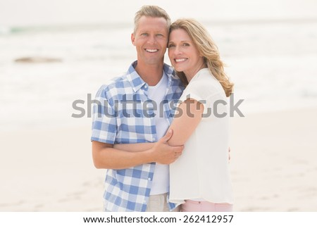 Casual man smiling at camera at the beach - stock photo