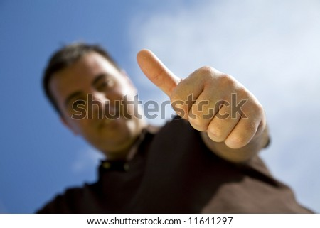 casual man smiling doing the thumbs up sign - focus on hand - stock photo