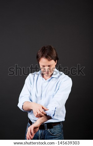 Casual man standing rolling up his shirtsleeves against a dark background with copyspace - stock photo
