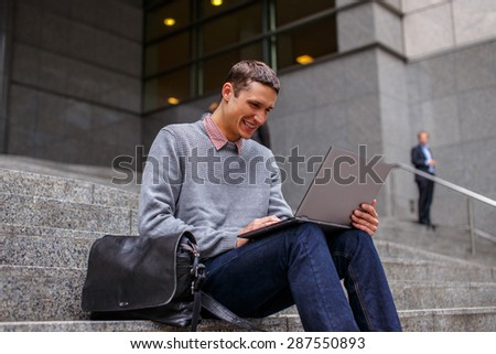 Casual man with laptop sitting on stairs. - stock photo
