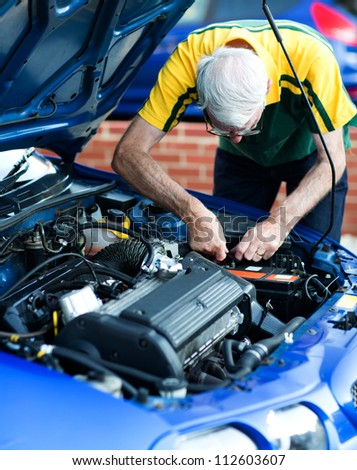 Casual man working on a car engine as a mechanic - stock photo