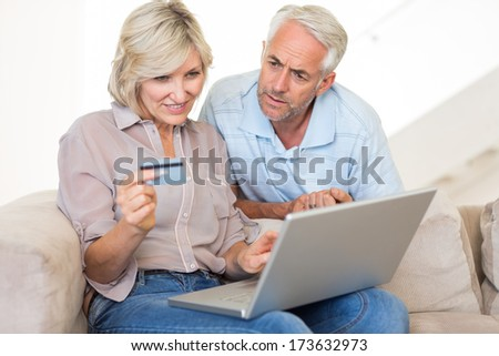 Casual mature couple doing online shopping through computer and credit card at home - stock photo