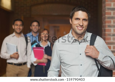 Casual mature student posing in corridor with his class in the background - stock photo
