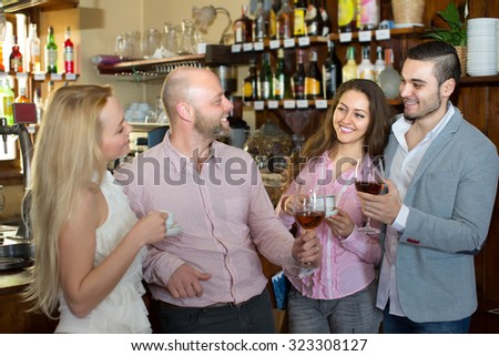 Casual meeting of happy smiling young adults at bar. Selective focus  - stock photo