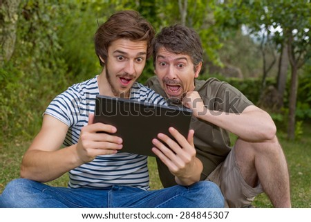 casual men surprised with a tablet pc, outdoor - stock photo