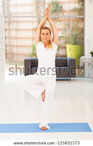 casual middle aged woman doing yoga at home - stock photo