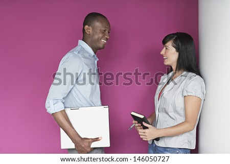 Casual multiethnic young male and female executives talking against pink wall - stock photo