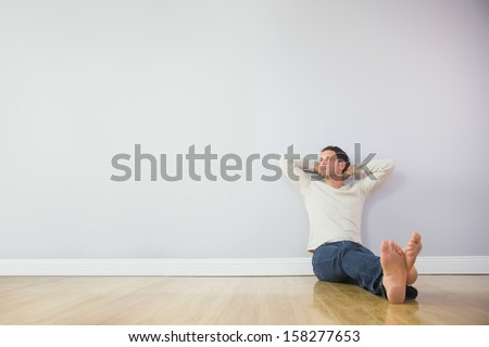 Casual pensive man leaning against wall with crossed arms in bright room - stock photo