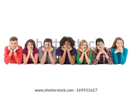 Casual people. Cheerful young multi-ethnic people lying on front and smiling while isolated on white - stock photo