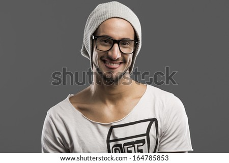 Casual portrait of a young man wearing a cap, over a gray background - stock photo