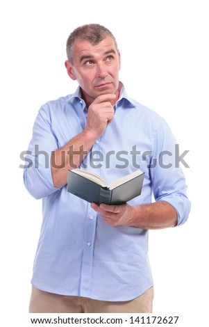 casual senior man contemplating with a book in his hands, looking away with a hand on his chin. isolated on white background - stock photo
