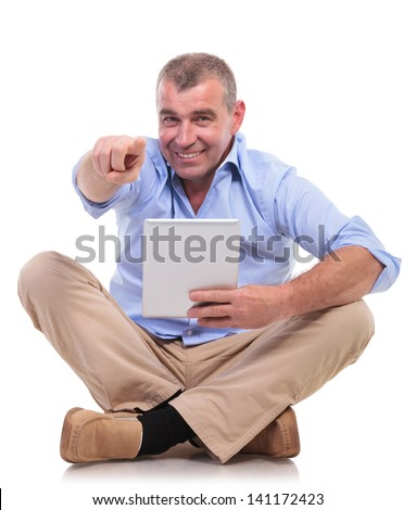casual senior man sitting on the floor with his legs crossed and holding his tablet while pointing and looking at the camera. isolated on white background - stock photo