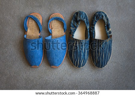 Casual shoes of men and women handmade with blue jean on gray grunge background - stock photo