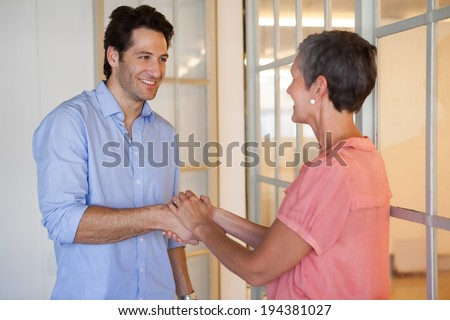 Casual smiling business people shaking hands in the office - stock photo