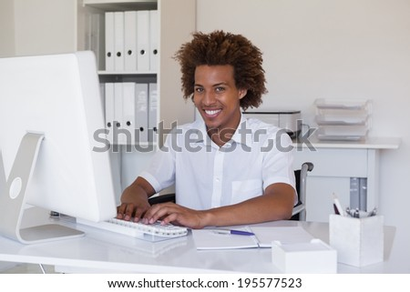 Casual smiling businessman in wheelchair working at his desk in his office - stock photo