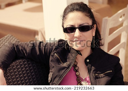 Casual smiling Caucasian woman with black sunglasses looking at the camera, vintage effect. - stock photo