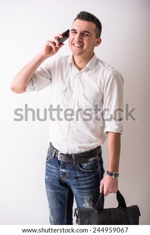 Casual smiling man with handbag is talking by phone on grey background. - stock photo