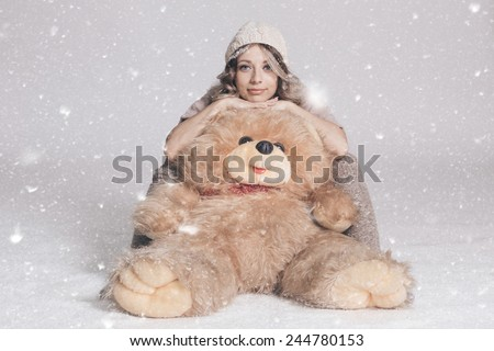 Casual smiling young woman in knitted clothes holding big soft teddy bear on snowy background. Studio shot - stock photo