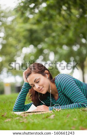 Casual student lying on grass reading on campus at college - stock photo