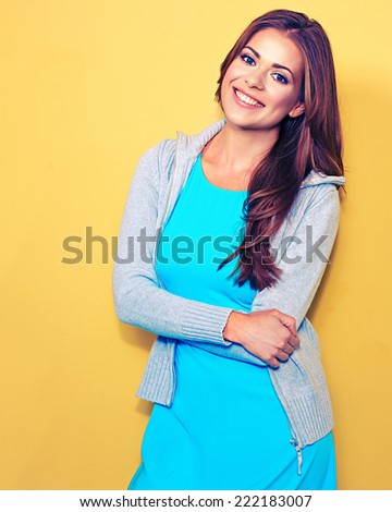 Casual style dressed young woman standing against yellow. Female smiling model. - stock photo